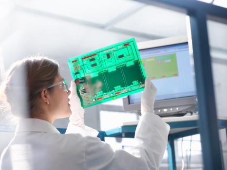 A female technician inspects a circuit board.
