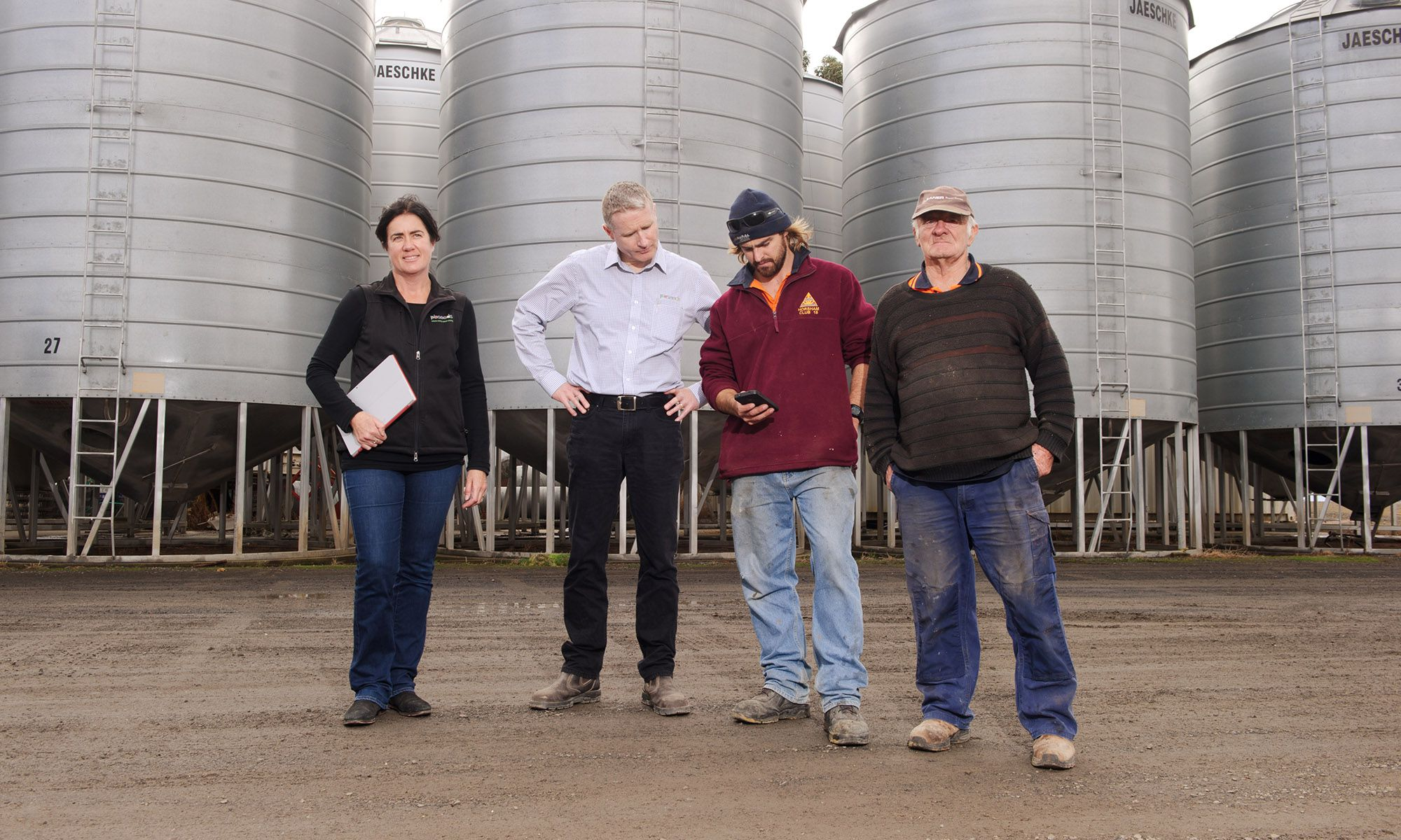 Four workers stand in front of grain silos