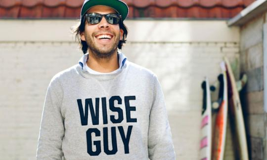 "guy wearing jumper with ""wise guy"" printed"