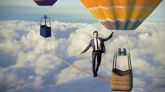 Man walking tightrope on hot air balloons