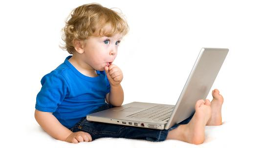 Child with lollipop sitting down using a computer
