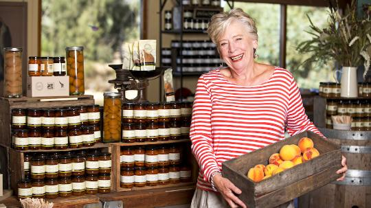 maggie beer holding box of peaches in food store