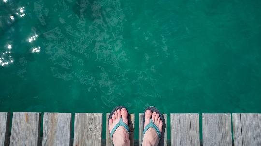 Feet in thongs on deck above water