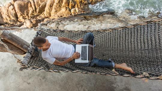Man on hammock using computer