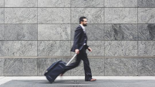 Man in suit walking with briefcase