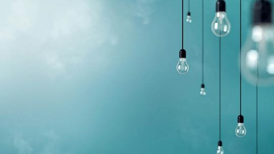 Lightbulbs hang in front of a blue wall