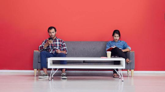 a man and a woman sit on opposite ends of a couch, writing and using a smartphone