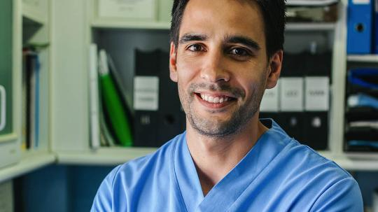 A young male doctor in scrubs smiles at the camera in an office