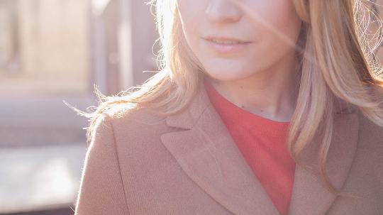 a close up photo of a blonde woman shown from the nose down with with sunlight behind her.
