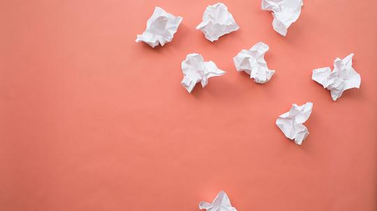 8 scrunched up pieces of paper on an orange backdrop