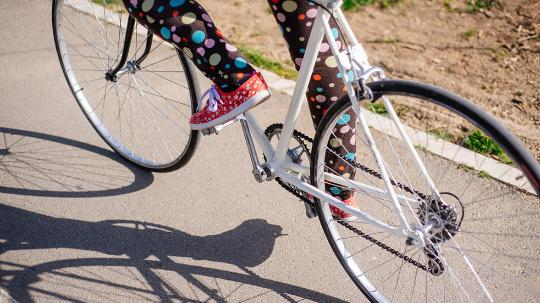 A close up image of a woman riding a bicycle.