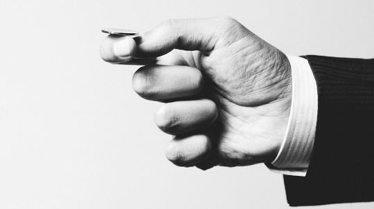 A black and white photo of a hand about to flip a coin