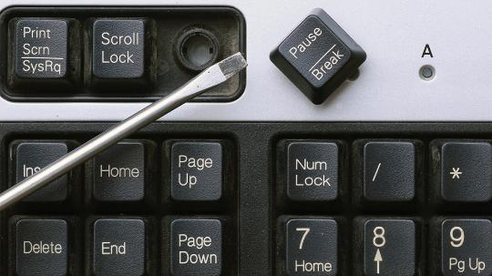 Keyboard with a broken key and a screwdriver next to it.