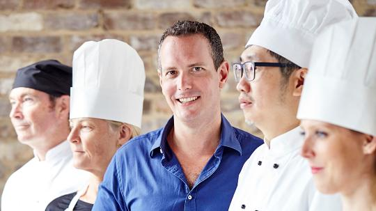 A smiling man standing amongst four people dressed as chefs.
