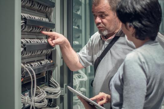 Two network engineers inspecting data cables.