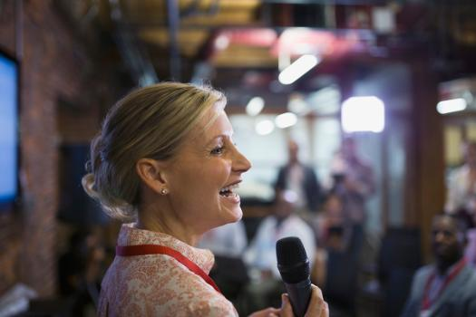 Business woman giving speech in front of peers holding a microphone.