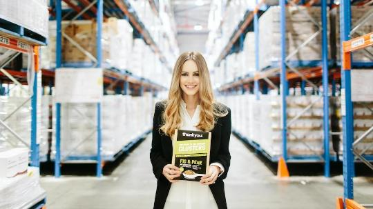 woman in cereal packet in manufacturing warehouse