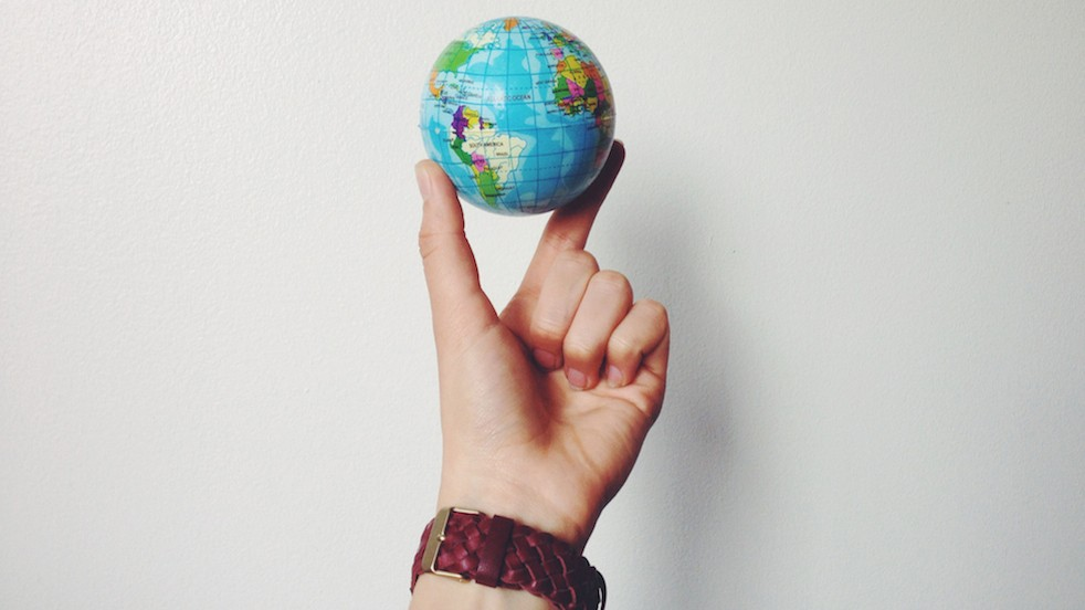small globe being held up by a hand