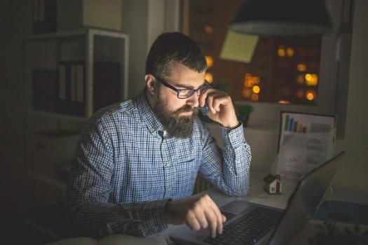 Small business owner working on a laptop at night