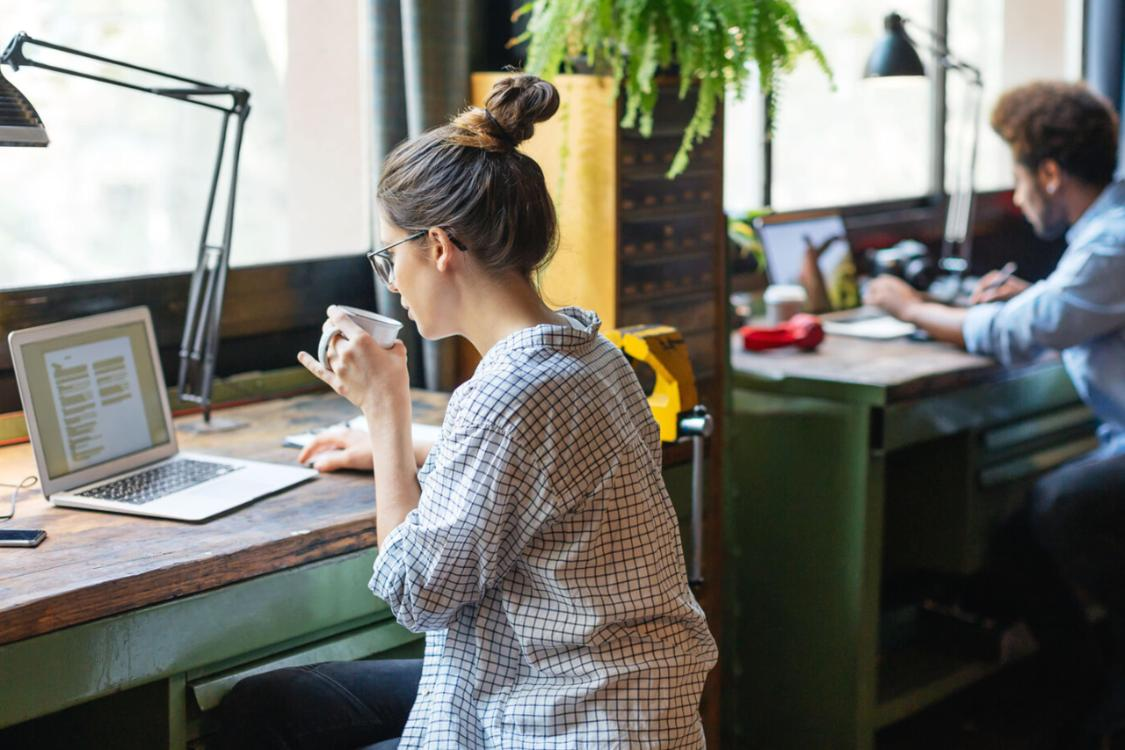 Woman drinks coffee while working on laptop