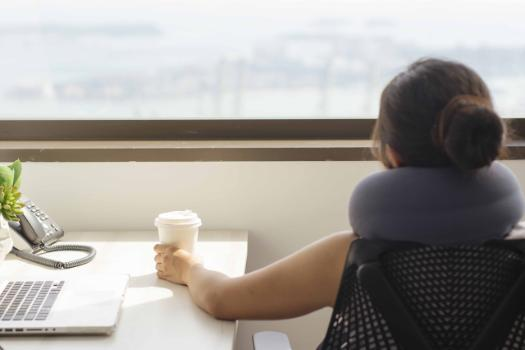 Woman drinks coffee and looks out of office window