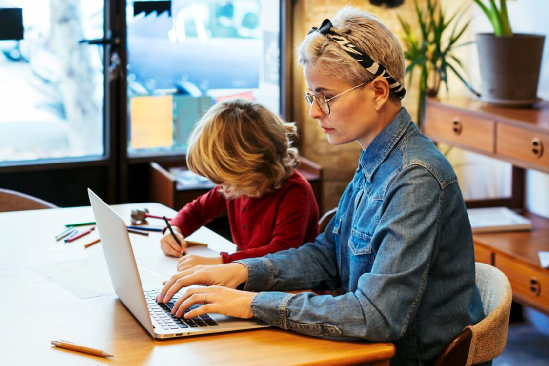 woman with her son works on a laptop