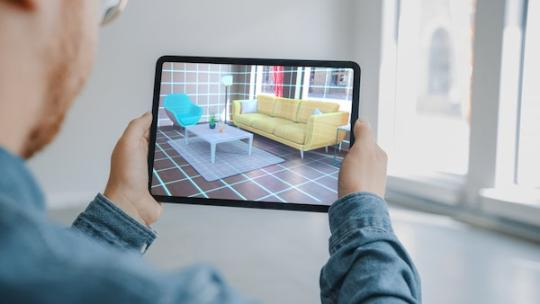 Man viewing furniture using augmented reality technology