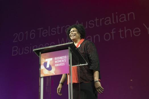 Andrea Mason laughing while standing behind a Telstra Business Women's Awards podium.
